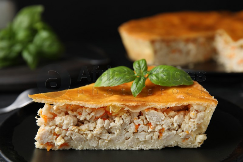 Piece of delicious pie with meat and basil in plate, closeup