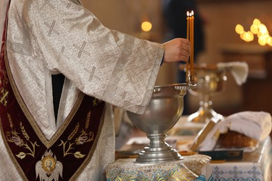 Priest taking burning candle in church, closeup. Baptism ceremony