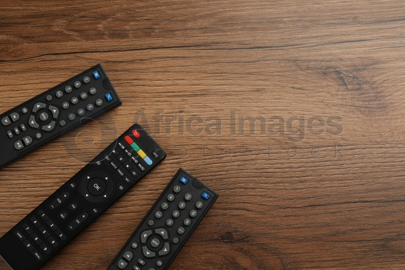 Modern tv remote controls on wooden table, flat lay. Space for text