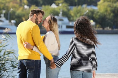 Man holding hands with another woman behind his girlfriend's back near river on sunny day. Love triangle