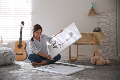 Decorator with pictures on floor in baby room. Interior design