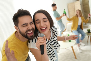 Happy couple singing karaoke with friends at home