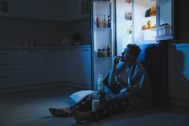 Young man eating cookies near open refrigerator in kitchen at night