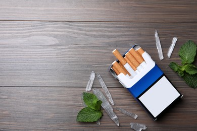 Pack of cigarettes, menthol crystals and mint on wooden table, flat lay. Space for text