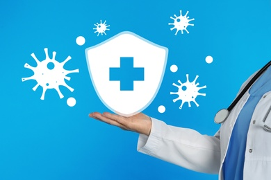 Immunologist and shield with cross as symbol of virus protection on light blue background, closeup