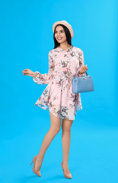 Young woman wearing floral print dress with stylish handbag on light blue background