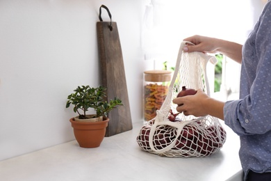 Woman taking red onion from mesh tote bag at countertop in kitchen, closeup