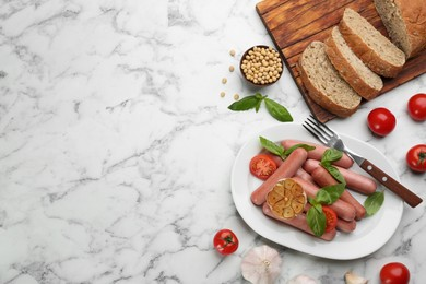 Flat lay composition with vegetarian sausages and vegetables on white marble table. Space for text