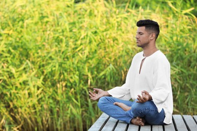 Man meditating on wooden pier outdoors. Space for text