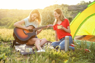 Young women resting with hot drink and guitar near camping tent in wilderness