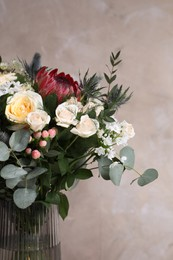 Beautiful bouquet with roses on beige background, closeup