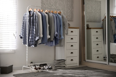 Dressing room interior with clothing rack and chest of drawers