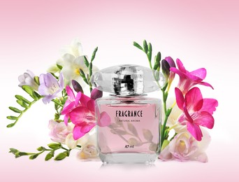 Bottle of luxury perfume and beautiful flowers on color background