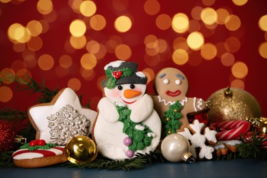 Sweet Christmas cookies and decor on dark table against blurred festive lights