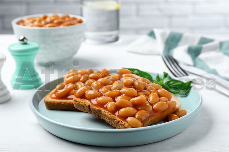 Toasts with delicious canned beans on white wooden table