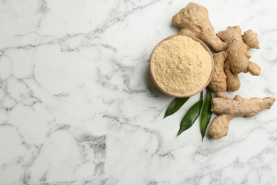 Dry ginger powder, fresh root and leaves on white marble table, flat lay. Space for text