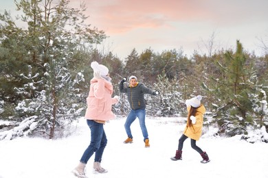 Happy family having snowball fight outdoors on winter day. Christmas vacation
