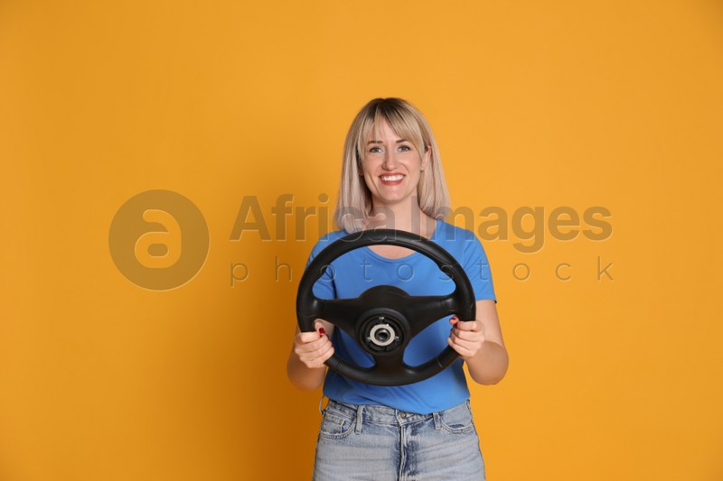 Happy woman with steering wheel on yellow background. Space for text