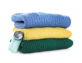 Modern fabric shaver and woolen clothes on white background