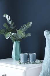Beautiful eucalyptus branches and candles on white table near blue wall. Interior element