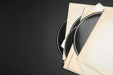 Vintage vinyl records in paper sleeves on black background, flat lay. Space for text