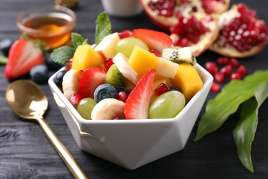 Delicious fresh fruit salad in bowl on black wooden table