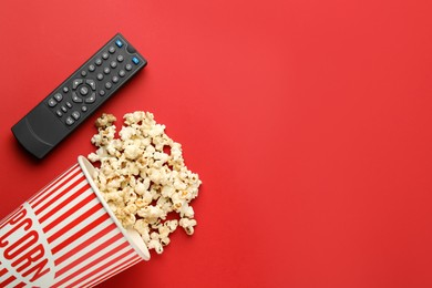 Remote control and cup of popcorn on red background, flat lay. Space for text