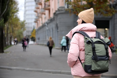 Young tourist with travel backpack in city on vacation. Space for text