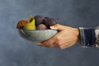 Woman holding bowl with tasty raw figs on light blue background, closeup