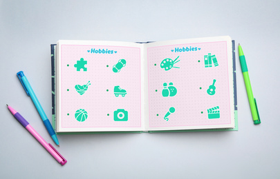 Open notebook with icons of different hobbies and pens on light background, flat lay