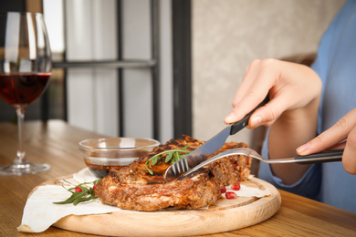 Woman eating delicious grilled ribs at wooden table indoors, closeup