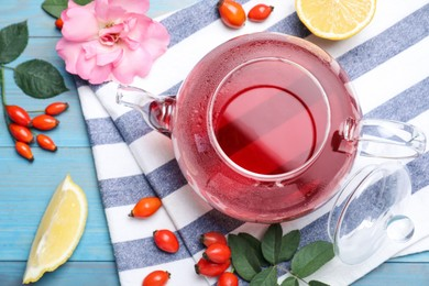 Fresh rose hip tea and berries on blue wooden table, flat lay