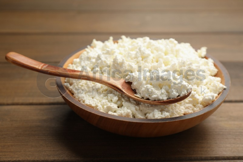 Delicious fresh cottage cheese on wooden table, closeup