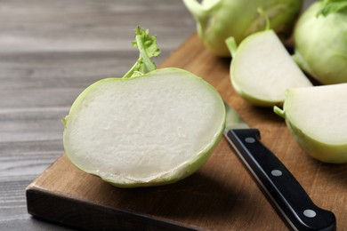 Whole and cut kohlrabi plants on wooden table, closeup