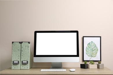 Comfortable workplace with modern computer near on table near white wall. Space for design