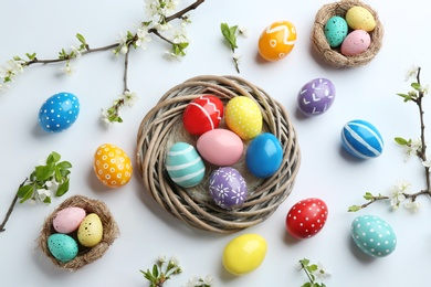 Flat lay composition with painted Easter eggs and blossoming branches on white background