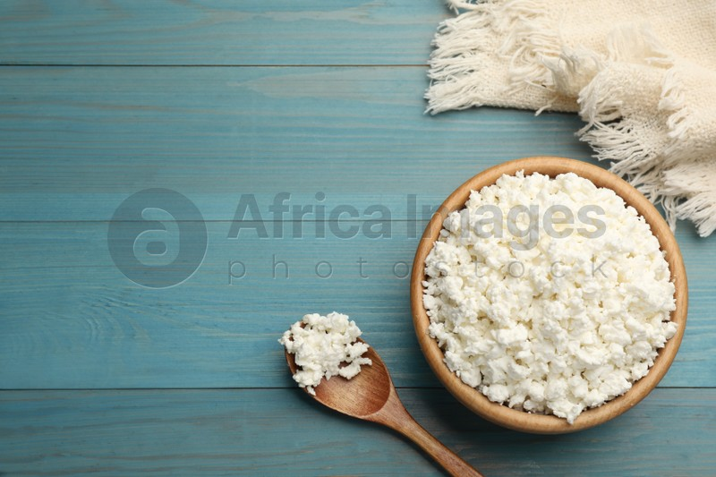 Delicious fresh cottage cheese on blue wooden table, flat lay. Space for text