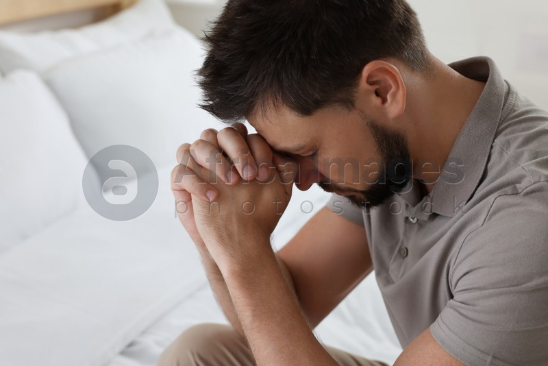 Religious man with clasped hands praying in bedroom