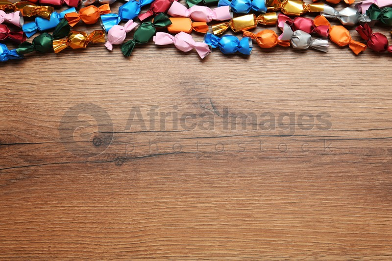 Many candies in colorful wrappers on wooden table, flat lay. Space for text