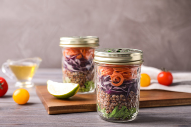 Glass jars with healthy meal on light grey wooden table