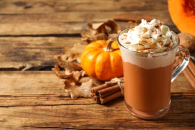 Delicious pumpkin latte on wooden table, closeup. Space for text