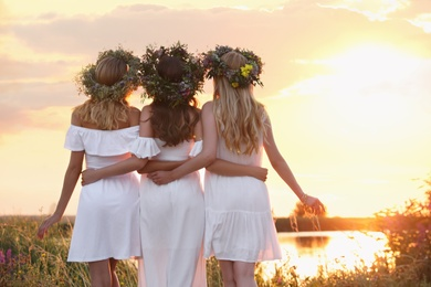 Young women wearing wreaths made of flowers outdoors at sunset, back view