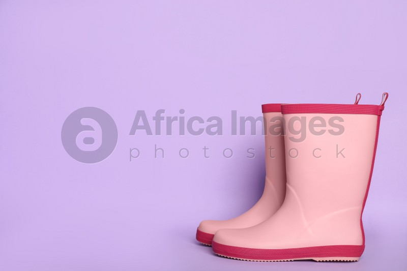 Pair of pink rubber boots on violet background. Space for text
