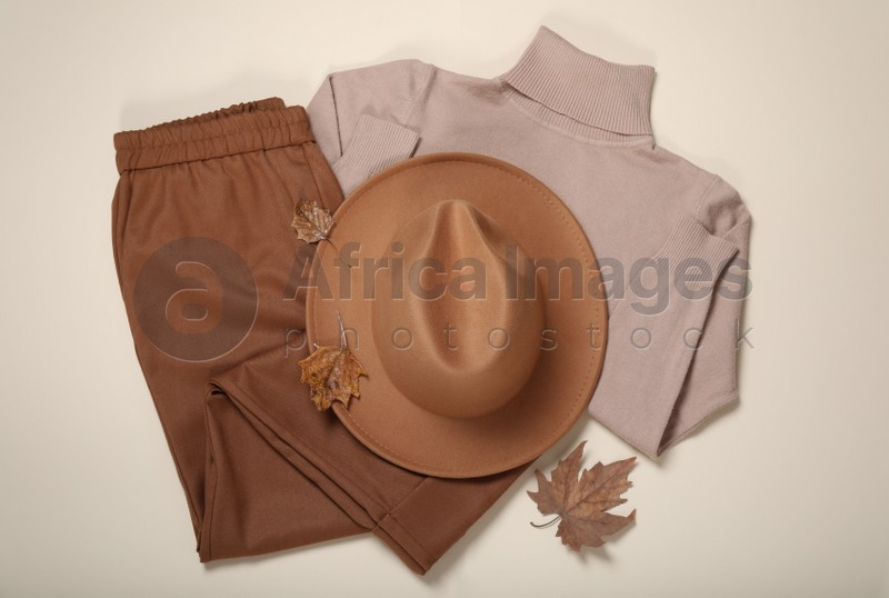 Flat lay composition with stylish hat and clothes on beige background