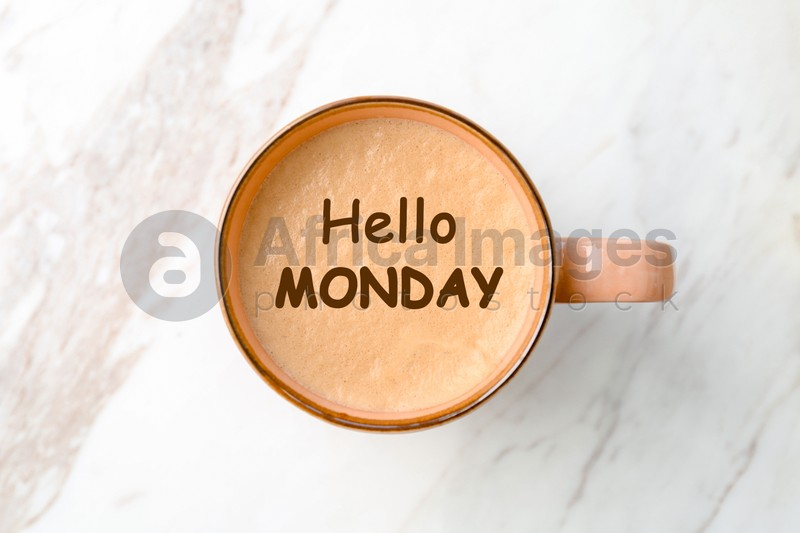 Hello Monday, start your week with good mood. Cup of freshly brewed aromatic coffee on white marble table, top view