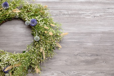 Beautiful wreath made of wildflowers on wooden background, above view. Space for text