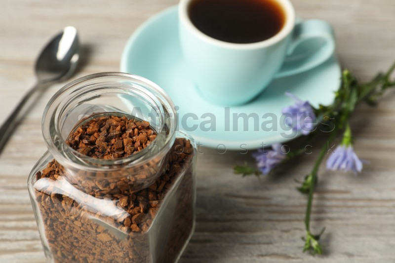 Jar of chicory granules on white wooden table, closeup. Space for text