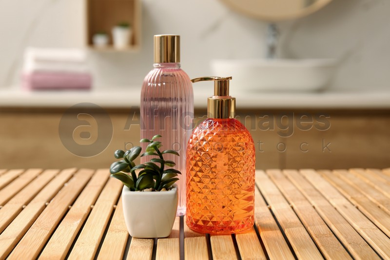 Glass dispenser with liquid soap, bottle of gel and plant on wooden table in bathroom