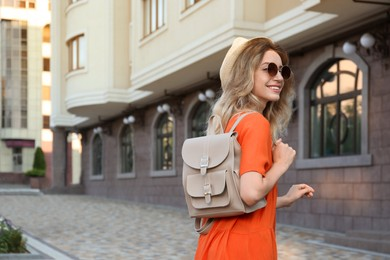 Beautiful young woman with stylish backpack outdoors. Space for text