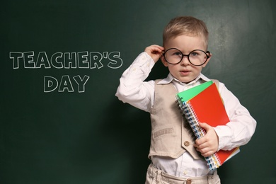 Cute little child wearing glasses near chalkboard with text Teacher's Day